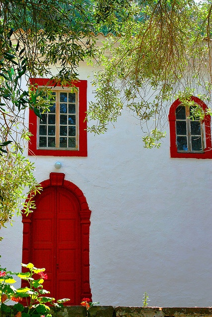 Facade with red decoration framed by leaves. Gaios, Paxos island, Ionian, Greece