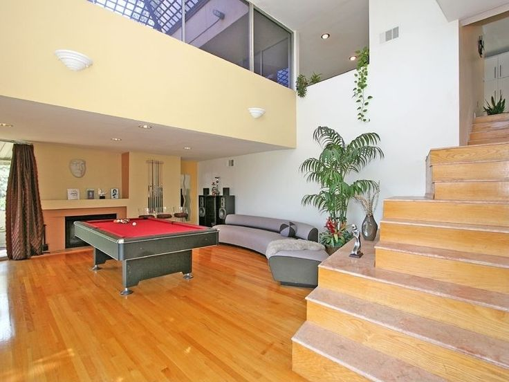 Eclectic Game Room with can lights, Wall sconce, Laminate floors, High ceiling, Loft