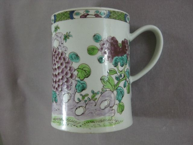 A fine and large Bow mug brightly painted in the famille rose style with chrysanthemums and foliage amongst rocks. A green diaper and flower head border to the rim and a grooved handle with a heart shape to its base. Unmarked  Circa 1752 Height 5 3/4""