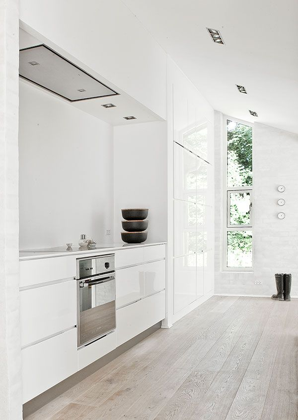 Kitchen: pale grey timber floorboards, gloss white handleless cabinets, exposed brick walls rendered and painted white, long narrow window on side of house