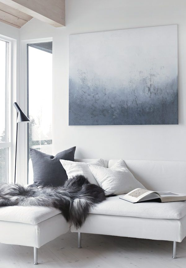 White sofa and sheepskin throw in the Norwegian home of Nina Holst / Stylizimo.