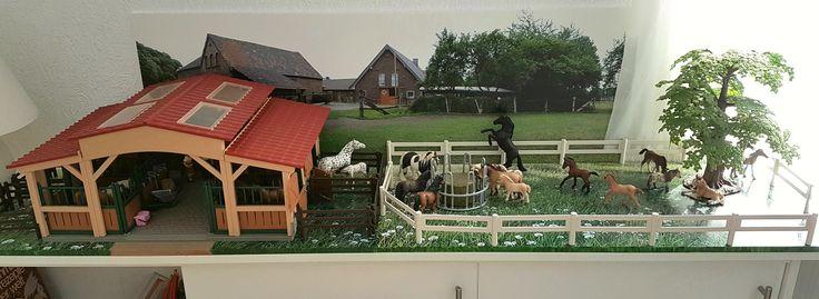 Mit Fotos können sich Spielsachen im Wohnraum sehen lassen. Ein Panoramabild auf einer Forex-Platte dient als Hintergrund, Fotos von Gras, auf Sperrholz geklebt, werden zum dekorativen Untergrund. Velour-d-c-fix auf der Rückseite verhindert Kratzer auf den Möbeln. Den Rand kann man einfach mit Acrylfarbe bemalen.