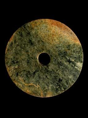 Jade disc, or Bi,  China, Neolithic period, Liangzhu culture, around 2500 BC  Stone rings were being made by the peoples of eastern China as early as the fifth millennium BC. Jade discs have been found carefully laid on the bodies of the dead in tombs of the Hongshan culture (about 3800-2700 BC), a practice which was continued by later Neolithic cultures. Large and heavy jade discs such as this example, appear to have been an innovation of the Liangzhu culture (about 3000-2000 BC)…