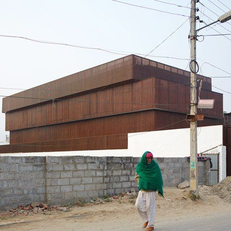 The stacked horizontal volumes that make up this house in Jammu, India, are clad in vertical timber battens to regulate the amount of sunlight that enters.