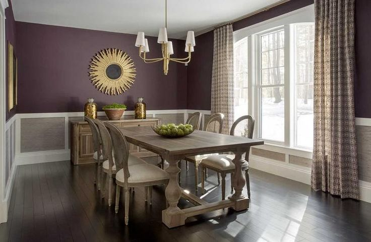 Grey and purple dining room features aubergine paint on upper walls and gray wainscoted panels on lower walls lined with a reclaimed wood sideboard and a gold sunburst mirror.