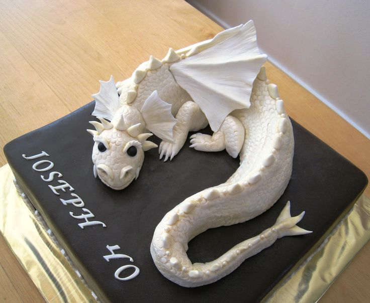 Dragon cake in pale gold and brown - This is my disaster dragon cake - I dropped the dragon in the floor after many, many hours of work....But I fixed it and it came out ok in the end. Its for my dear brothers 40th birthday. Filled with raspberry mousse and white chocolate mousse. Dragon is RKT, gumpaste and fondant, it's dusted with pale gold luster dust but it's hard to see in the pics.Cake is covered with chocolate fondant, 12 inches. TFL!