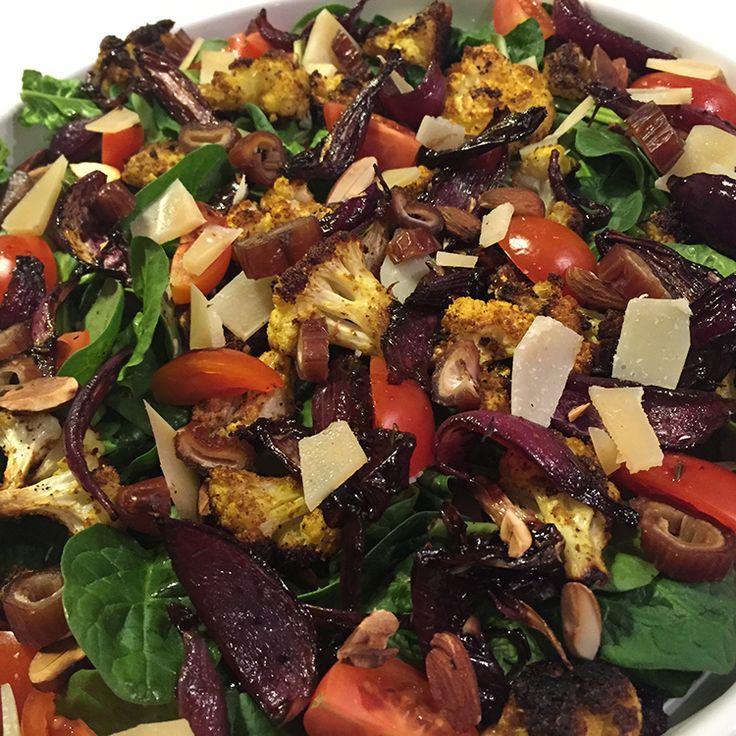 Karrybagt blomkålssalat med frisk spinat, cherrytomater, balsamico bagte rødløg, ristede mandler, dadler og parmesan flager.