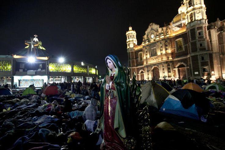 Una estatua de la Virgen de Guadalupe sobresale entre numerosos peregrinos que duermen al aire libre cerca de la Basílica de Guadalupe en la ciudad de México, a primeras horas del sábado 12 de diciemb