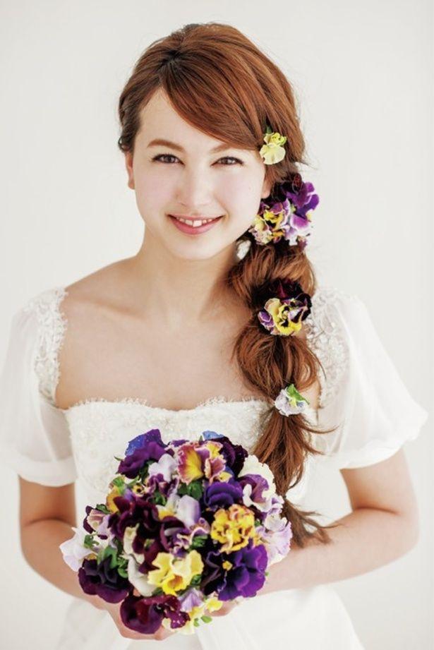 片側に流したヘアをところどころ結び、ヘッドコサージュを飾っただけ。けれど、花嫁らしい主役の華やかさにあふれて。ゲストの歓声が聞こえてきそう!...