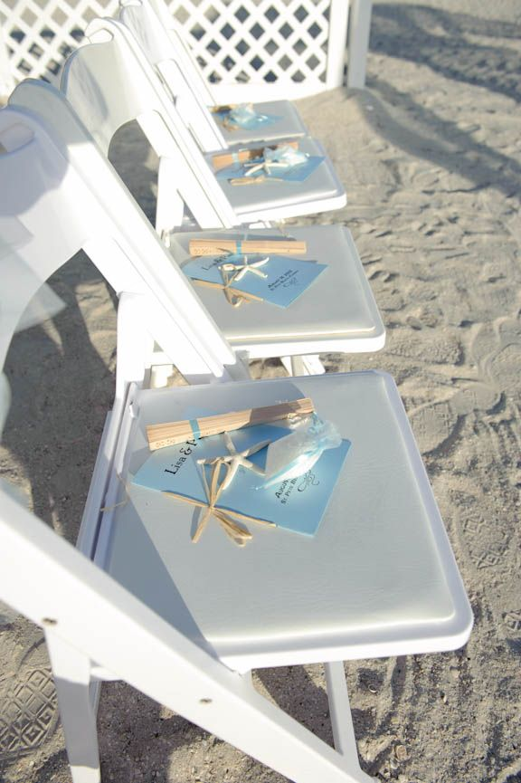Florida beach wedding programs and fans on white folding chairs for the wedding ceremony