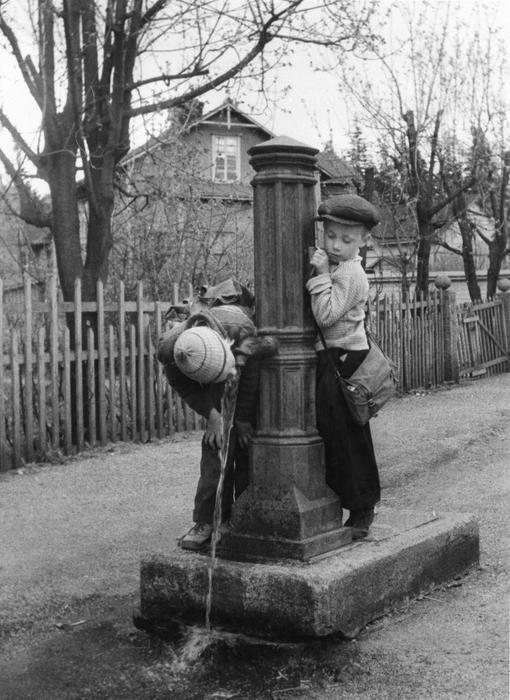 Barn vid en vattenpost i Böle i hörnet av Kyllikkigatan och Bölegatan på 1950-talet. Fribrunnar installerades i slutet av 1880-talet i områden där hushållen saknade vattenledning. Från fribrunnarna fick man hämta vatten gratis. Foto Eino Heinonen, 1950-talet. Helsingfors stadsmuseum.