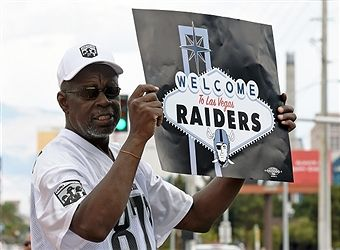 Oakland Raiders fan Davi Tole of Nevada displays a sign to passing motorists on the Las Vegas Strip near the Welcome to Fabulous Las Vegas sign after National Football League owners voted 31-1 to approve the team's application to relocate to Las Vegas during their annual meeting on March 27, 2017 in Las Vegas, Nevada. The Raiders are expected to begin play no later than 2020 in a planned 65,000-seat domed stadium to be built in Las Vegas at a cost of about USD 1.9 billion.