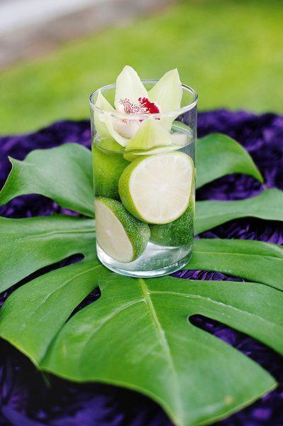 pieza central sobre hoja verde  Cilindro de cristal -limones y orquidea sumergida