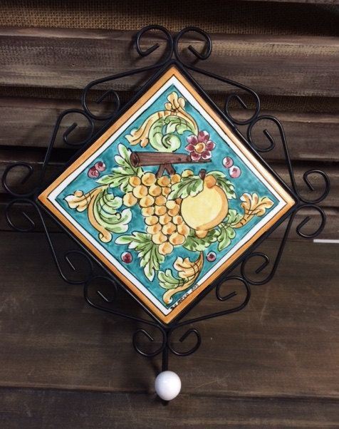 Iron frame with decorated tile and hook. by Bluanticoceramics