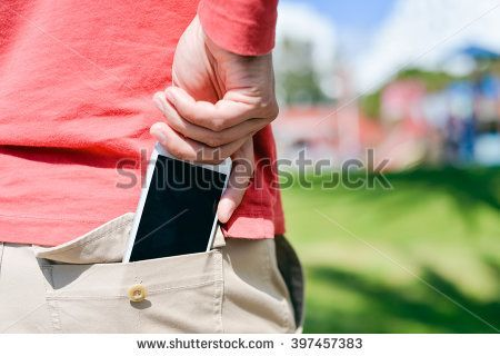 Closeup on man hand holding taking a smartphone in the back pocket on sunny background outdoors