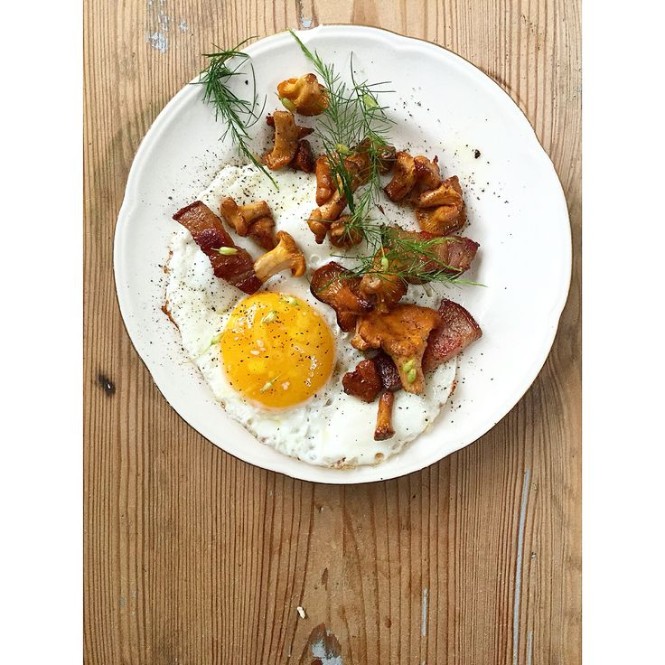Fried egg with chanterelle, bacon and asparagus flower