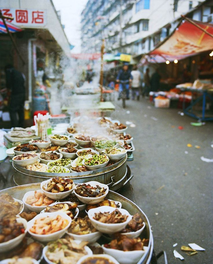 A series of small dishes at a food stand on Sipailou Street near Yu Gardens, Shanghai. The dishes include deep-fried shrimp, red-braised pork, and fava beans.