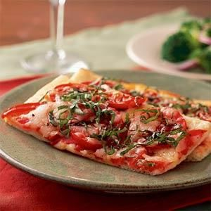 Make a thin and crispy pizza in under 30 minutes with refrigerated pizza dough, plum tomatoes, mozzarella, and basil.