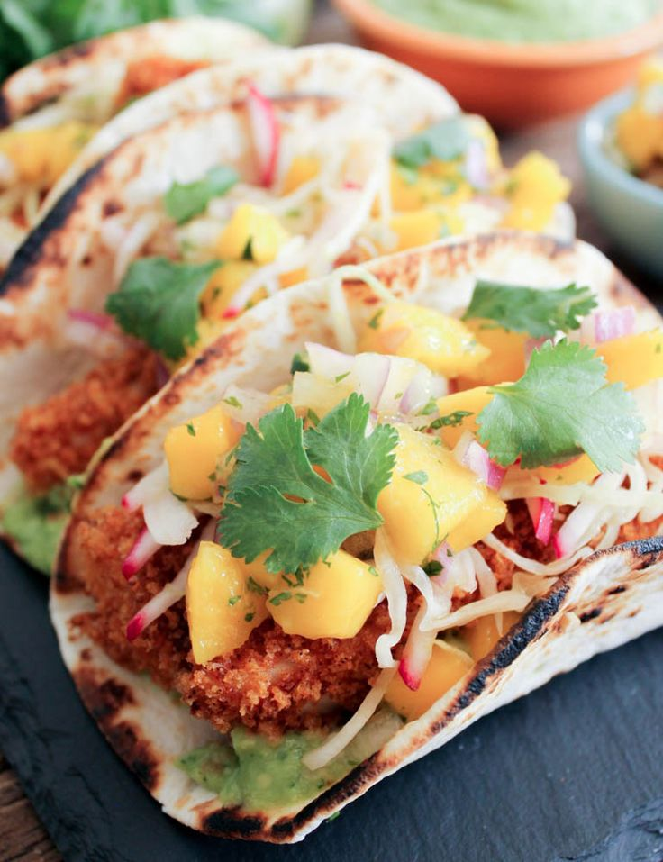 Fish Tacos with Mango Salsa | One of the iconic Baja California dishes is the fish taco.  Golden brown white fish (such as tilapia, cod or halibut) are tucked into a corn tortilla with a bright fresh mango salsa and a avocado sauce.  One bite and you'll be in love with this meal. @DomesticateMe