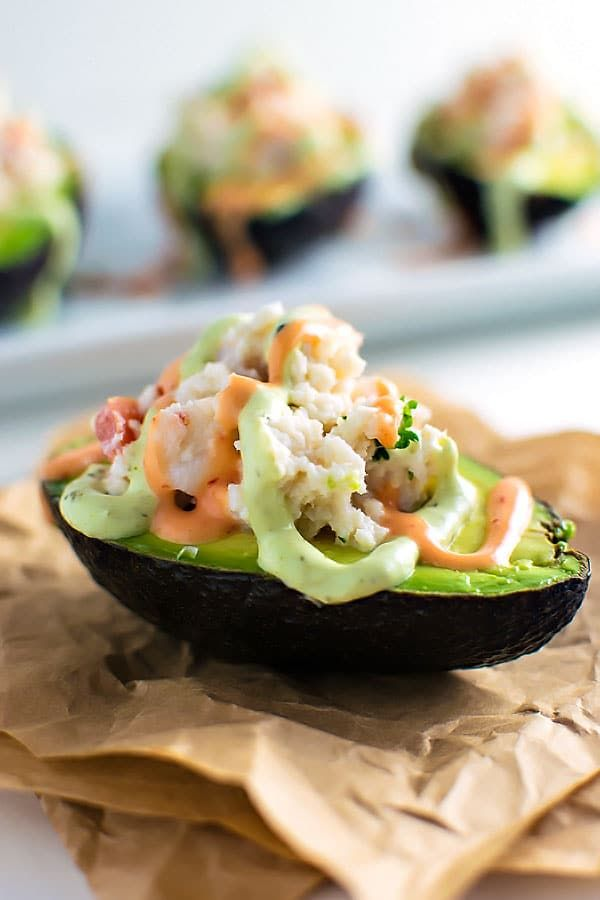 Halved avocados filled with chopped shrimp, fresh crab, and tomato and then drizzled with sriracha and avocado creams on top.