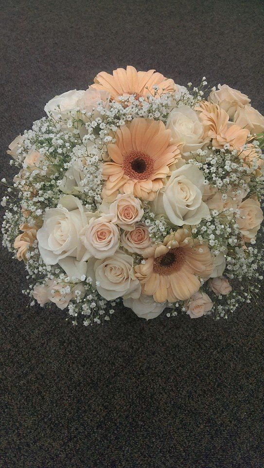 Vintage bridal bouquet created by Penny at Woodland Floral in Kalispell,Montana. Using cream gerbera daisies, white roses and peach spray roses and lots of babies breath.. Stems were wrapped with lace.