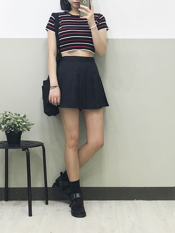 The high waist of the skirt balances out the crop top and makes the girl appear taller.