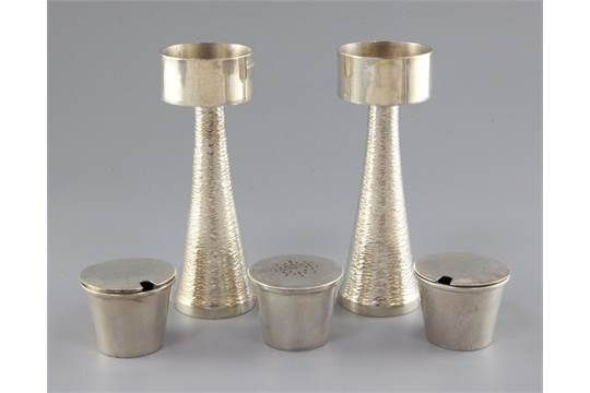 A pair of 1970's silver candle holders and a three piece silver condiment set by Graham Watling o