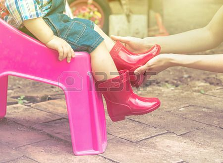 Mother wearing red color boots to baby, Family scene mother and baby