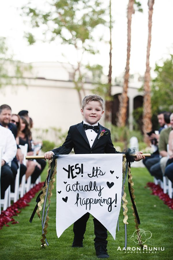 Riviera Palm Springs Wedding, Destination Wedding Photographer.  Rock and Roll themed wedding.  Banner saying Yes! It's actually happening! Ringer Bearer
