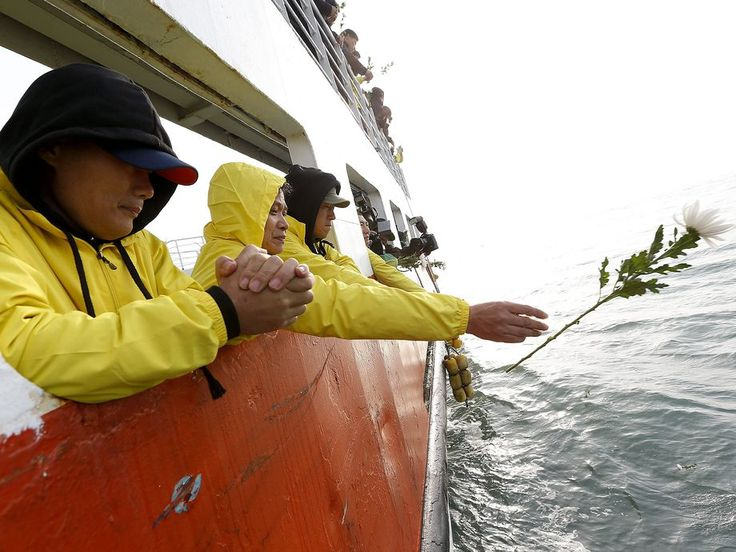 Relatives of victims aboard the sunken ferry Sewol throw offerings into the sea off Jindo Island, South Korea. The ferry capsized and sank on April 16, 2014, killing 295 people.  Pool photo by Jeon Heon-Kyun