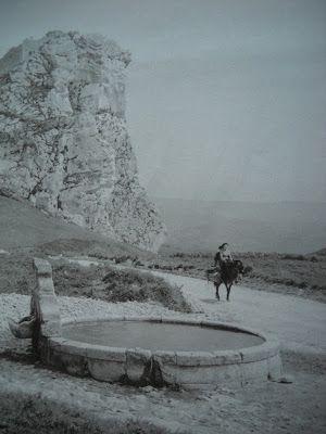 LE SICILIANE DI EZIO QUIRESI, Una donna cavalca il suo asino portando con sè un…