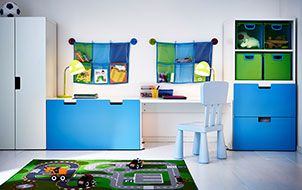 A children's room with a wardrobe, storage benches and a desk in white and blue