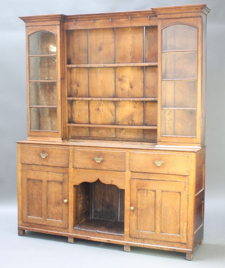 "Lot 950, An 18th Century dresser with raised inverted breakfront top with moulded cornice, the centre section fitted 3 shelves flanked by a pair of cupboards fitted shelves enclosed by a pair of arched panelled doors, the base fitted 3 long drawers above a recess flanked by a pair of cupboards 81""h x 66 1/2""w x 17""d est £200-400"