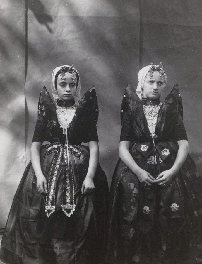 """Meisjes in Axelse klederdracht. Het rechter meisje draagt over de ondermuts en het oorijzer een """"trekmuts"""".    Het linker meisje draagt de """"rondemuts"""" of """"hernhuttermuts""""  Beiden zijn gekleed in zondagse dracht.  De opname is gemaakt in 1913 te Amsterdam tijdens het klederdrachtenfeest. Dit was onderdeel van festiviteiten rond de 100 jarige onafhankelijkheid van Nederland. 1813-1913."""