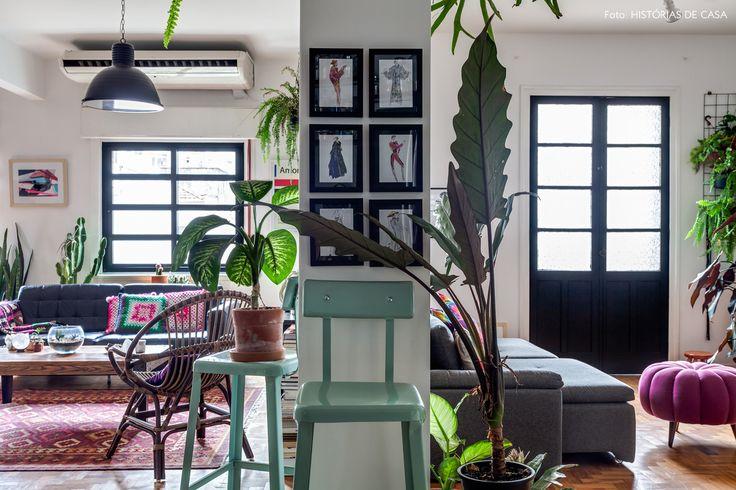 apartamento reformado com sala integrada, janelas pintadas de preto e muitas plantas