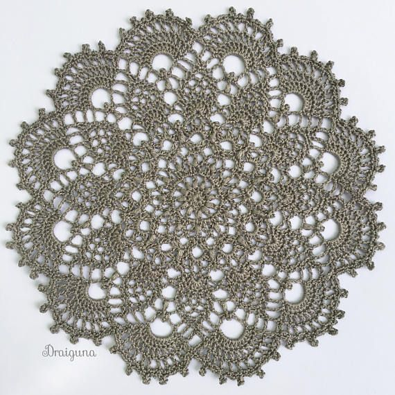 This doily is made with size 10 cotton thread. The color available is gray. There are a few different stitches in this doily including puff stitches, clusters, front post single crochet, and picots. It measures 8 and has been lightly starched. The design is called Dawnglow by Julia Hart. If you would like to make it here is a link to the free pattern- http://www.draiguna.com/p/dawnglow-photo-tutorial.html?m=1