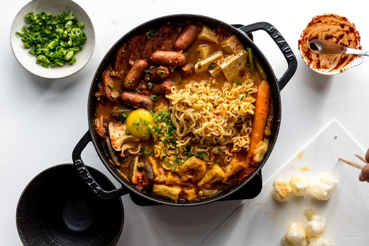 Our take on a popular Korean hot pot dish: budae jjigae, or army stew! A comforting spicy stew with spam, sausages, tofu, mushrooms, and ramen noodles.