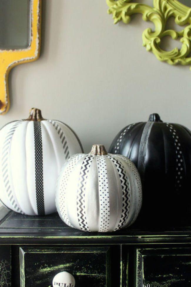 Черные и белые тыквы украшенные ленточками.
