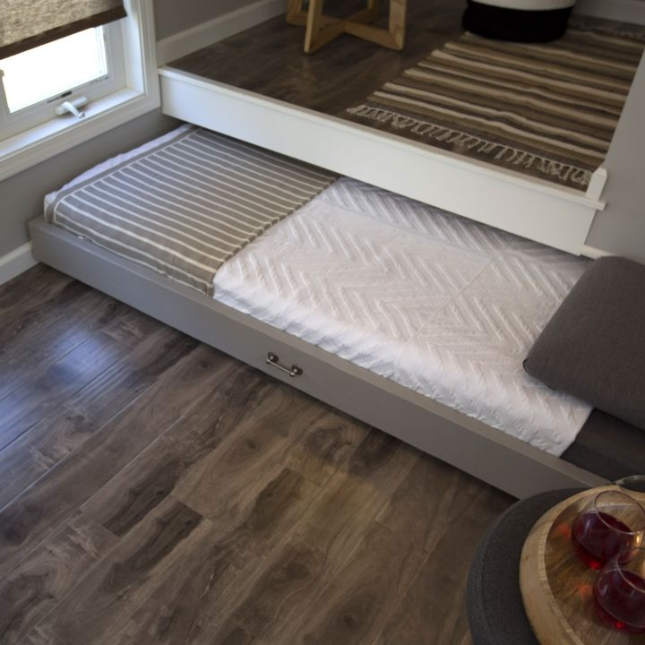 A pull-out bed helps create a sleep space when you need it, but doesn't take up any additional square footage in your tiny house! | Tiny Homes