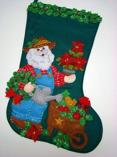"This wonderful Christmas Stocking called ""GARDENING SANTA"" is made of felt applique on cloth and beautifully decorated with hand sewn sequins and beads. Portions of this stocking are stuffed creating a three dimensional appearance. Many hours of work went into completing the beautiful heirloom stocking measuring approx. 21"" diagonally and 10"" across the top. Lots of room to stuff. Perfect for any gardening enthusiast."