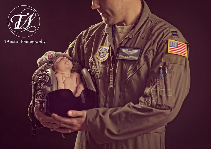Newborn photo of baby Lilly in daddy's military flight helmet in the studio