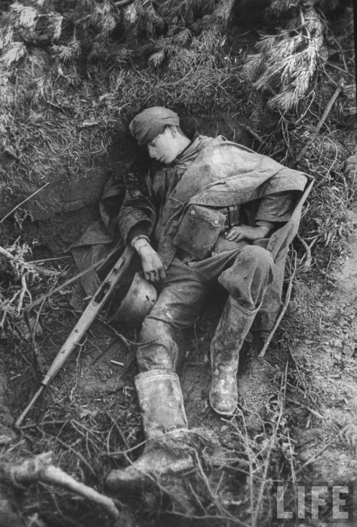 A dead teenage German soldier killed during a British offensive in Holland (Spring 1945). Note the two bullet holes in his helmet and his empty rifle.