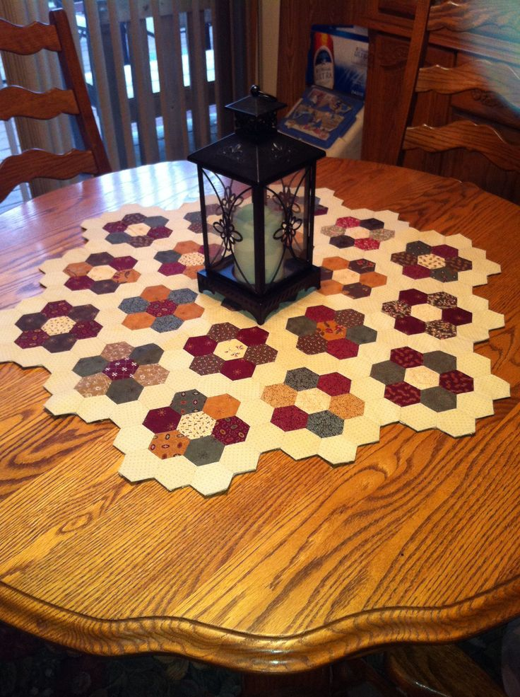 1 inch Hexagon Table Topper made from 5 inch Charm squares cut into 2 1/2 inch squares. Birthday gift for my sister.