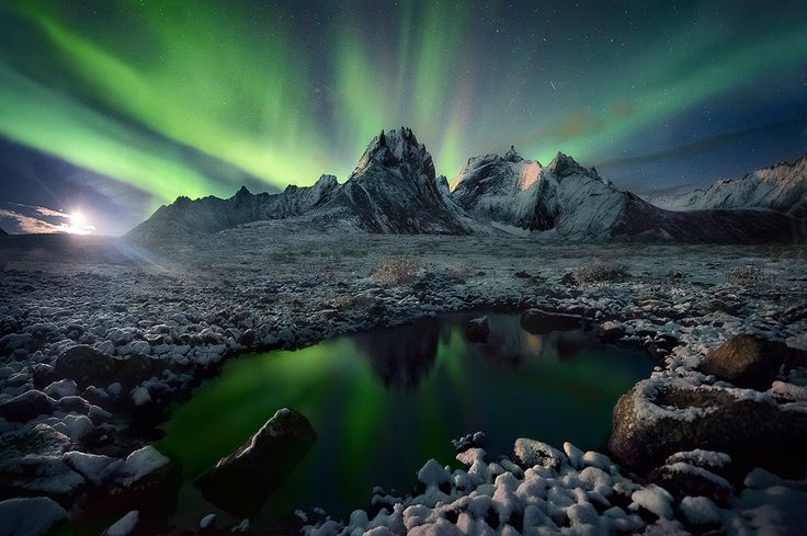 Imagination by Marc  Adamus on 500px Light of a faint moon rises illuminating the mountains of Yukon's North as the Aurora shines overhead. The image is a stitch using part of 3 images across for an ultra-wide view.