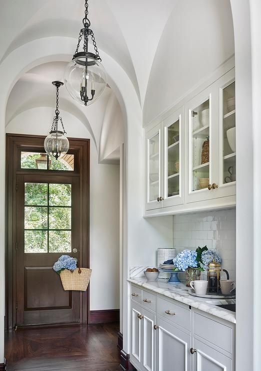 Stunning butler's pantry features a barrel ceiling dotted with Small Amphora Bell Jar Pendants illuminating glass front upper cabinets and white bottom cabinets paired with white marble countertops and a white glazed tiled backsplash laid out in a brick pattern.