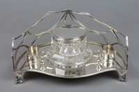Lot No 673 A Victorian silver ink stand, the pierced gallery enclosing a cut glass silver mounted inkwell, 2 receptacals with pen stand, on raised bracket feet, sold £380