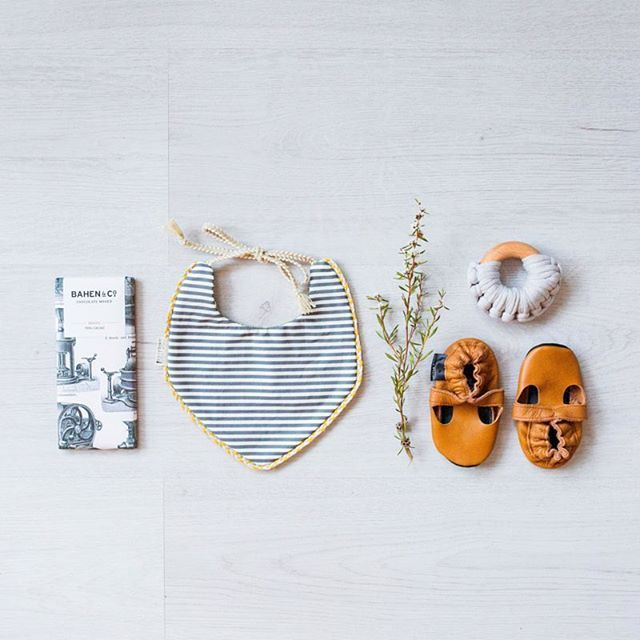 Baby accessories, soft sole shoes, heirloom bib, teether and chocolate.