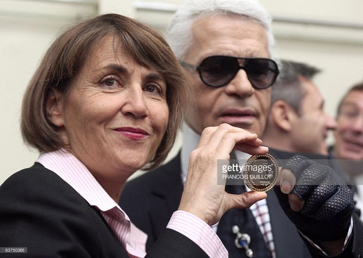 German fashion designer Karl Lagerfeld (R), flanked by French Culture Minister Christine Albanel, presents on November 19, 2008 at Paris Hotel des Monnaies, a gold coin worth 5,900 euros (7,440 US dollars), representing French legend designer Gabrielle 'Coco' Chanel (1883-1971) unveiled today. French Culture Minister Christine Albanel and Karl Lagerfeld were invited by the CEO of 'Monnaie de Paris' (The French Mint) Christophe Beaux to present the 10,000 copies first mint collection series…