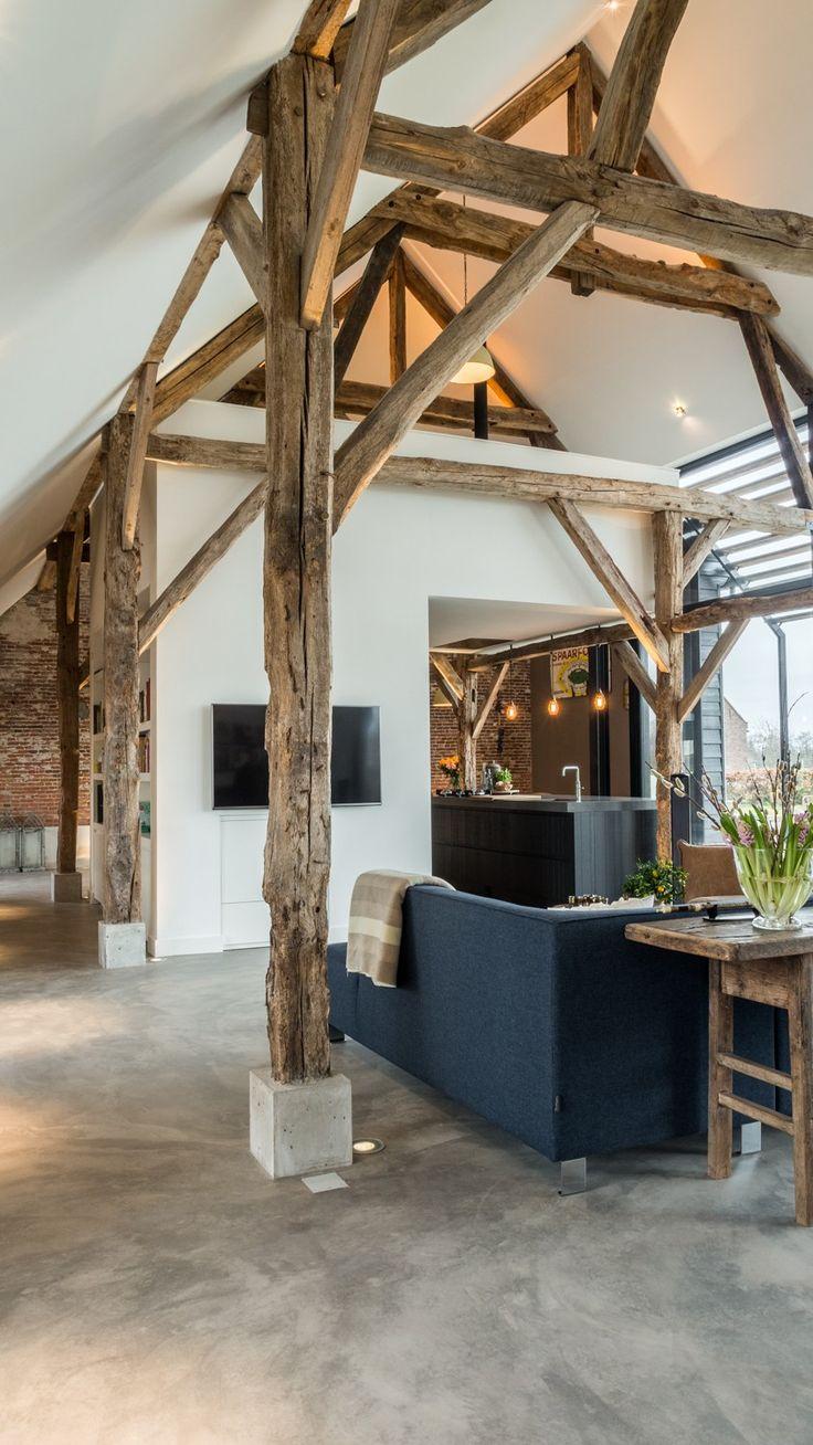 Betonnen sokkels beschermen de onderkanten van de houten spanten. Verlichting bij de houten spanten accentueert de structuur van de houten balken.