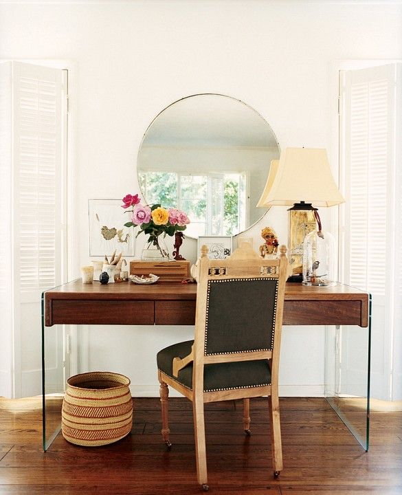 Workspace with modern glass-sided desk, classic side chair, and round mirror.